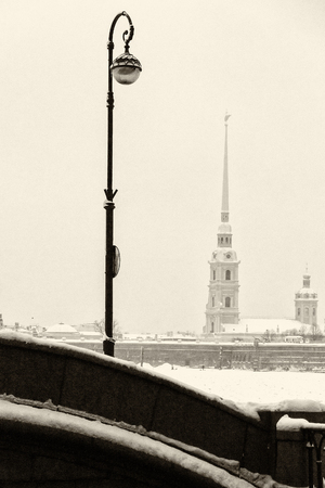 Touristic landmark in Saint Petersburg, Russia: Peter and Paul fortress and Cathedral by a winter day with a lantern at the foreground. Black and white retro photo. Фото со стока