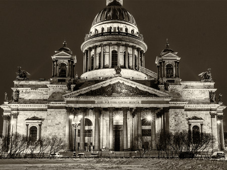 Old historical architecture landmark and touristic spot in Saint Petersburg, Russia: Saint Isaac's Cathedral by a winter night illuminated. Black and white retro photo.