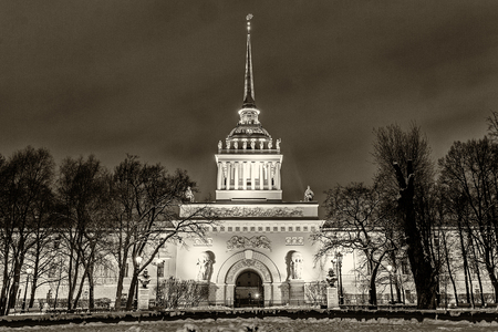 Landmark in St Petersburg, Russia: historical Admiralty building by winter night with park and trees in front of it and cloudy sky as a background. Black and white retro photo. Фото со стока - 89343616