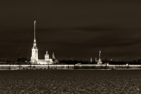 Landmark in St Petersburg, Russia: Peter and Paul fortress by winter night with Neva river in ice and snow in front of it and cloudy sky as a background. Black and white retro photo.