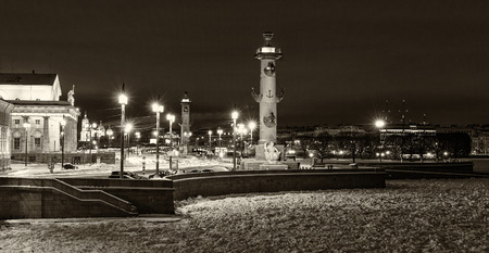 Landmark in St Petersburg, Russia: Spit of Vasilievsky Island by winter night with historical buildings, rostral columns, lanterns and granite embankment. Black and white retro photo. Фото со стока - 89343619