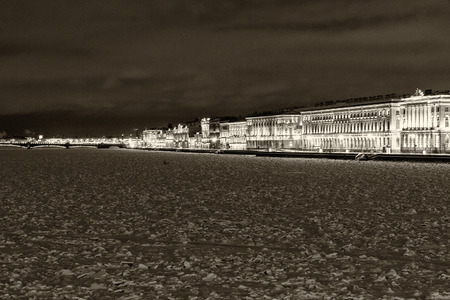 Landmark in St Petersburg, Russia: Neva river embankment by winter night with the Winter Palace, Neva in ice and snow and a bridge at the horizon. Black and white retro photo.