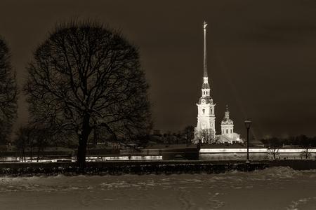 dom: Point de repère à Saint-Pétersbourg, Russie: la forteresse Pierre et Paul et Dom illuminée visible de la flèche de l'île Vassilievski par une nuit d'hiver. Photo rétro noir et blanc. Banque d'images