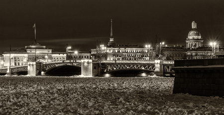 Landmark in St Petersburg, Russia by winter night: Neva river covered by ice and snow, the Palace bridge and historical city center illuminated. Black and white retro photo.