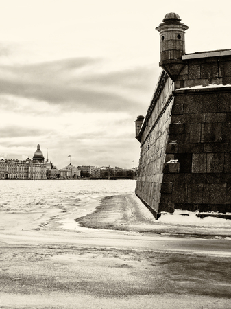 Landmark in St Petersburg, Russia: Peter and Paul fortress wall by winter day, Neva river in ice, sky with clouds and historical center of the city as a background. Black and white retro photo.