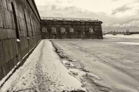 Landmark in St Petersburg, Russia: Peter and Paul fortress wall by winter day, Neva river in ice, sky with clouds and downrtown as a background. Black and white retro photo. Фото со стока