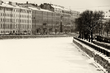 St Petersburg, Russia: the Fontanka river embankment by a winter day covered by ice and snow with old architecture historical buildings and trees around.  Black and white retro photo. Фото со стока