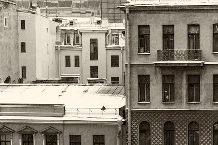 Facades of old apartment buildings (old architecture) in St. Petersburg, Russia, on a winter day. Windows of different shapes and roofs covered by snow. Black and white retro image. Фото со стока