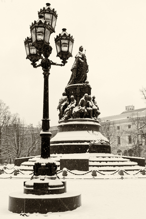 Landmark in St. Petersburg, Russia: Queen Catherine the Great monument in the square by a winter day covered by snow with old vintage lantern near it.  Black and white retro photo. Фото со стока