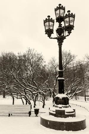 Historical landmark and touristic spot in Saint Petersburg, Russia: the old vintage lantern in the Ostrovsky square by a winter day with snow which covers everything around. Black and white image.