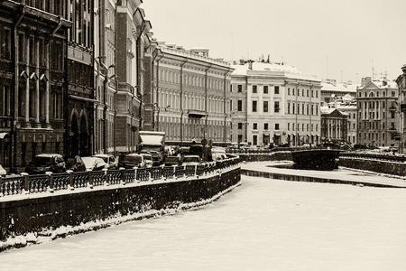 Saint Petersburg, Russia: the Moika river embankment by a winter day covered by ice and snow with old architecture historical buildings around. Black and white retro photo.