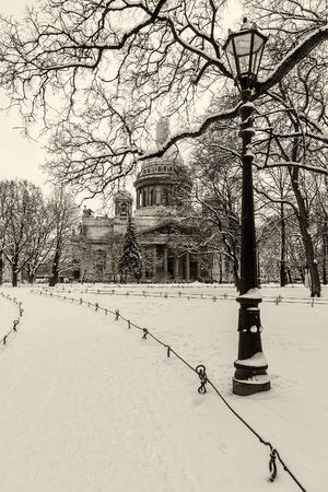 Architecture landmark  in St Petersburg, Russia: Saint Isaac's Cathedral and park in front of it by winter day with vintage lantern and trees covered by snow.  Black and white retro photo.