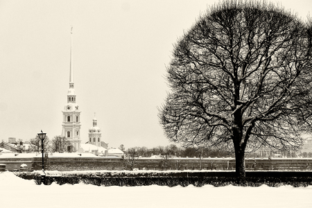 Touristic landmark in Saint Petersburg, Russia: Peter and Paul fortress and Cathedral by a winter day with lot of snow around. Black and white retro photo.