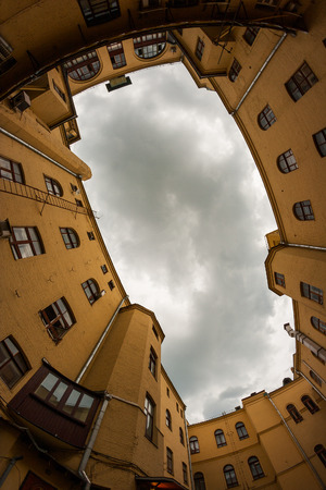 View on the old architecture buildings and cloudy sky from the ground. Walls form a frame for the sky. Фото со стока
