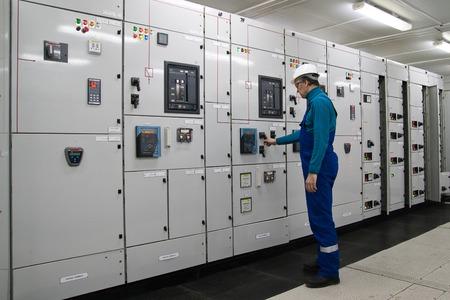 electricidad industrial: El hombre est� en la subestaci�n de distribuci�n de energ�a el�ctrica Foto de archivo
