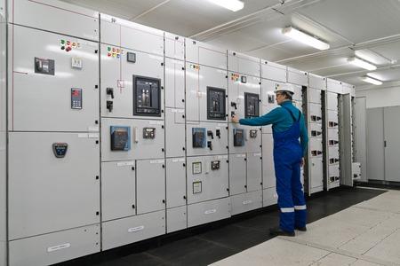 De mens bevindt zich in een onderstation voor de distributie van elektrische energie Stockfoto