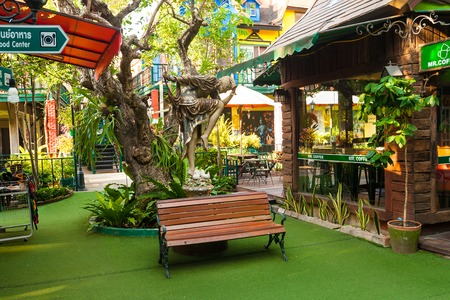 Pattaya, Thailand - December 06, 2018: Bench and statue are near cafe