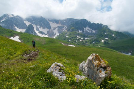Tourists walk along the path in the mountains of the North Caucasus.