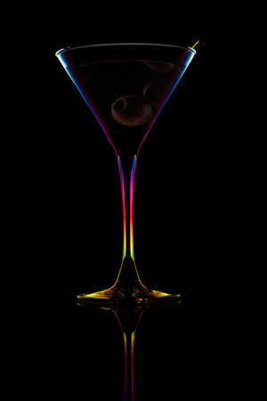 Martini with olive isolated on black background with spectrum light photo