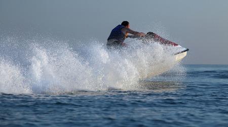jet skier: Man drive on the jetski. Sunset light