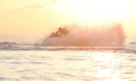 water skier: Man drive on the jetski. Sunset light