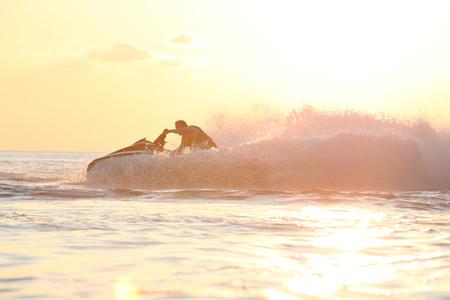 moto acuatica: Mecanismo impulsor del hombre en el jetski. la luz del atardecer