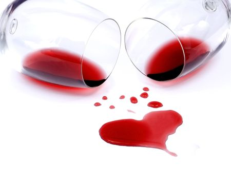 Red wine spilled from glasses forming heart shape photo