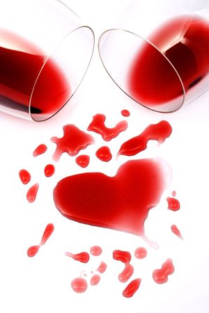 Red wine spllied from glasses forming a heart shape