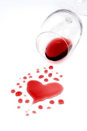 Red wine spilled from glass forming a heart shape photo