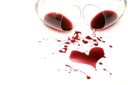 Red wine spilled from glasses forming a heart shape
