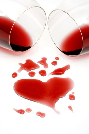 Red wine spilled from two glasses, forming a heart shape photo