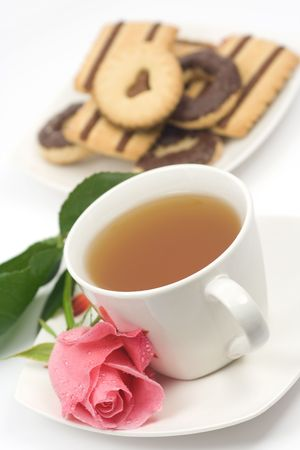 Cup of tea with one rose flower and chocolate cookies photo