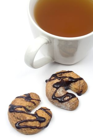 Two homemade chocolate glazed cookies and a cup of tea photo