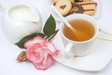 comida inglesa: Copa de Ingl�s t� con galletas de chocolate, leche y una rosa flores