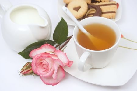 morning tea: Cup of english tea with chocolate cookies, milk and a rose flower Stock Photo