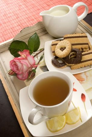 Tea cup served with cookies and a rose photo