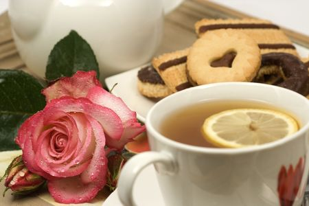 Cup of tea served with cookies and a rose flower