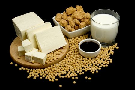 Soy sauce, tofu, soy meat supplement and soybeans on black background