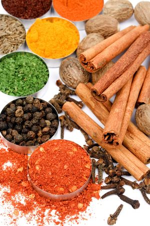curry spices: Ground pepper, cinamon sticks, cloves and other spices on white background Stock Photo
