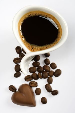Cup of espresso coffee with heart shaped chocolate candy photo