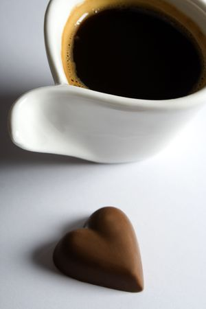 Cup of espresso coffee with heart shaped chocolate candy Stock Photo