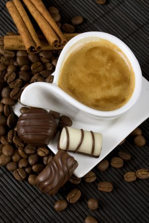Cup of coffee with chocolate candies, coffee beans and cinnamon sticks