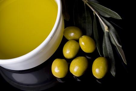 aceite de oliva: Aceite de oliva y aceitunas verdes sobre fondo negro Foto de archivo