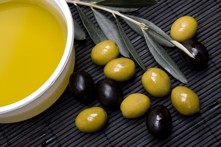 Extra virgin olive oil with green and black olives photo