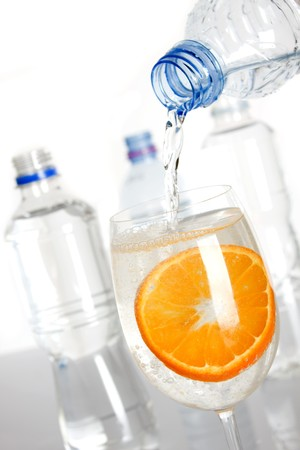Bottled water poured in a glass with slice of orange photo