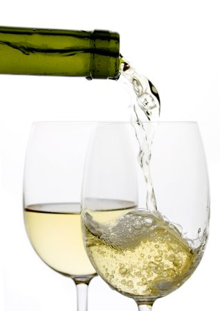 White wine poured in a glass over white background Reklamní fotografie