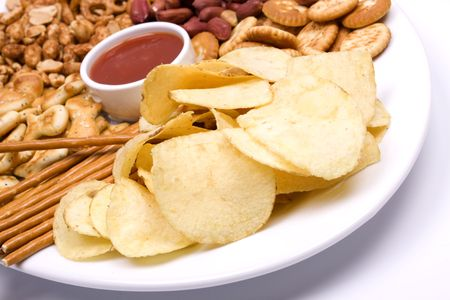 Potato chips and salty snacks served with hot salsa dip photo