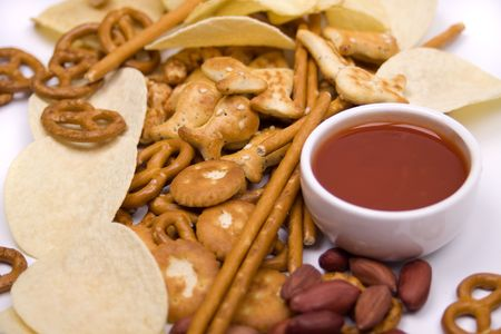 Potato chips and salty snacks with hot salsa dip sauce photo