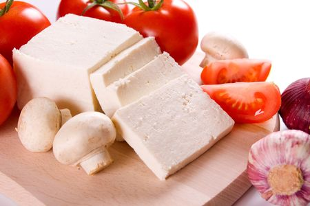 feta: White cheese with tomato, mushrooms and garlic on wooden board