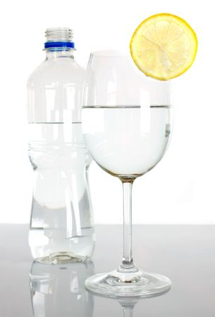 Bottle and glass of water with lemon slice on white background photo